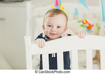 Toned portrait of smiling 1 year old baby boy in cot looking in camera