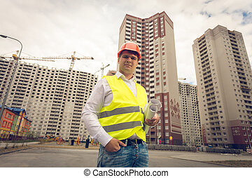 Toned portrait of young smiling engineer standing on building site