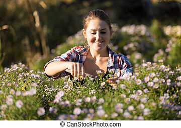 portrait of young woman cutting flowers at garden
