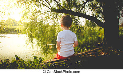 Toned rear view photo of little boy fishing on the river at sunset