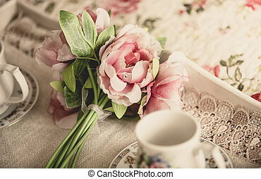 retro styled photo of pink flowers lying on tray with ...