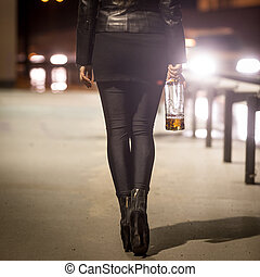 Toned shot of sexy girl with bottle walking by the road at night