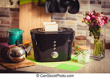Toned shot of toaster with fresh brad on decorated kitchen