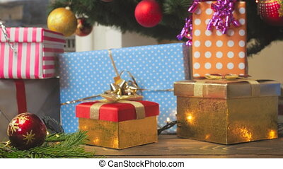 Toned video of decorated Christmas tree and colorful gift...
