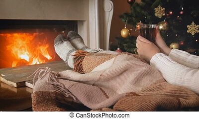 Toned video of woman lying on sofa next to burning fireplace...