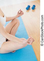 Toned woman in lotus pose at fitnes