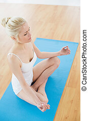 Toned woman sitting in lotus pose a