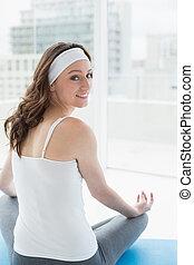 Toned woman sitting in lotus pose at fitness studio