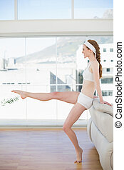 Toned woman stretching leg in fitness center - Side view of...