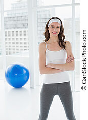 Toned woman with hands folded in fitness studio