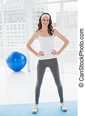 Toned woman with hands on hips standing in fitness studio
