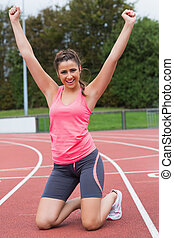 Toned young woman cheering on the running track - Full...