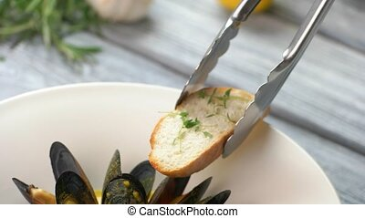Tongs put bread near mussels. Mussels and slices of...