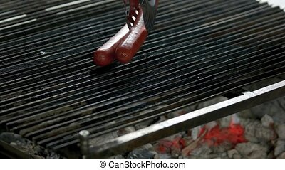 Tongs putting sausages on grill. Meat products close up.