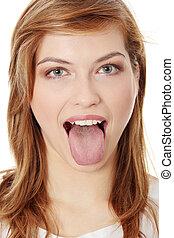 Tongue - Young cheerful girl showing tongue