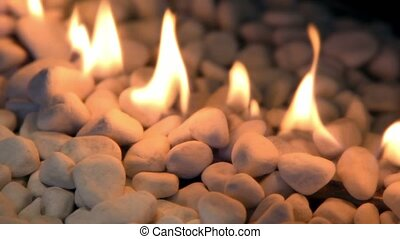 Tongues of flame at white stones pile, closeup view