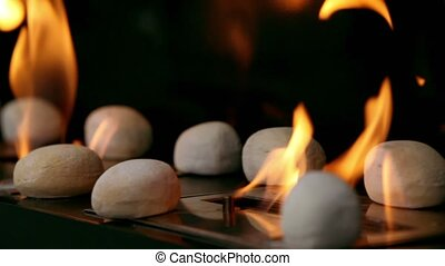Tongues of flame go through slot in metal plate with stones on it
