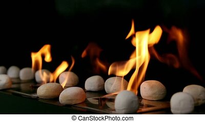 Tongues of flame go through slot in metal plate with stones...