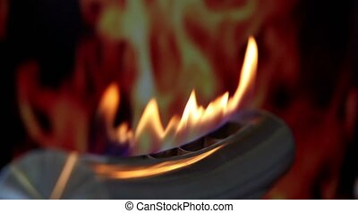 Tongues of flame go through slot in metal tube at background of image of fire