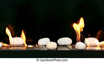 Tongues of flame go through two slots in metal plates with stones on it