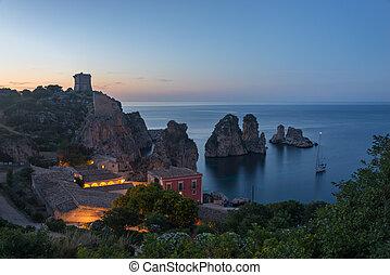 Tonnara and Faraglioni rocks in Scopello at dusk