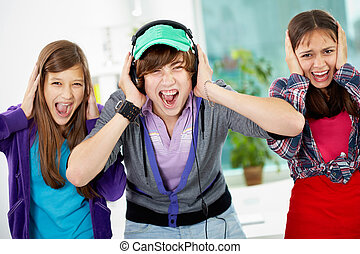Too loud - Teenagers screaming and covering their ears as...
