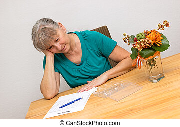 Too many drugs - desperated woman sitting at a table with...