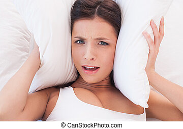 Too much noise. Beautiful young woman covering ears by pillow because of noise
