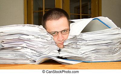 Too much paperwork - Sad man drowning in paperwork - looking...