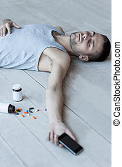 Too much pills. Top view of young man lying on the floor and holding a mobile phone in his hand while bottles with pills laying near him