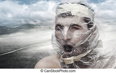 Too much pollution - Young man in the desert with a bag on...
