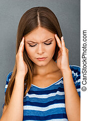 Too much stress. Depressed young woman holding hands on her forehead while standing against grey background