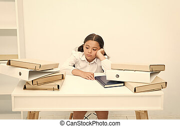 Too much to learn. Girl child tired exhausted sit at table near pile of books white background. Schoolgirl tired of studying and reading books. Kid school uniform tired face not want continue reading
