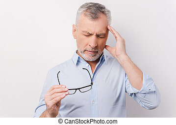 Too stressful day. Frustrated senior man in shirt touching head with fingers and keeping eyes closed while standing against white background