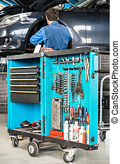Tool Cart With Male Mechanic Repairing Car