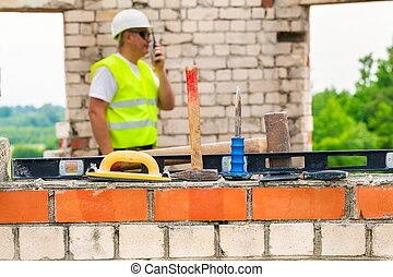 Tools and equipment with construction worker in background
