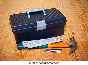 Tools box, hammer, nails and folding ruler on wooden background