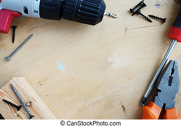 Tools for home renovation on a wooden desk. Hammer, screws and screwdriver.