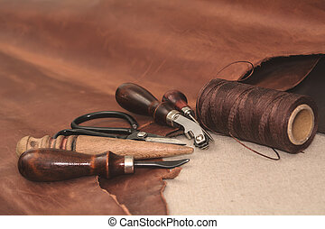 Tools for leather crafting and pieces of brown leather. Manufacture of leather goods