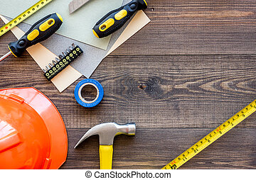 Tools for repairing and helmet on wooden desk background top...