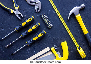 Tools for repairing on black stone desk background top view