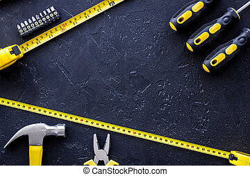 Tools for repairing on black stone table background top view copyspace