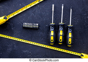 Tools for repairing on black stone table background top view