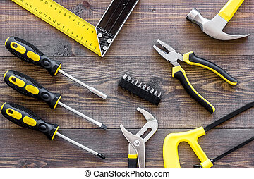 Tools for repairing on wooden desk background top view