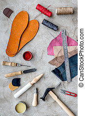 Tools for repairing shoes on grey stone desk background top view