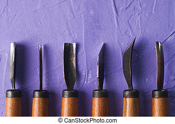 Handicraft background, tools for wood carving, carvings