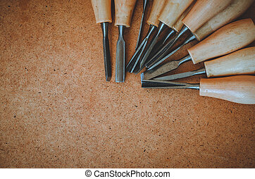Tools for woodcarving on brown rough background top view