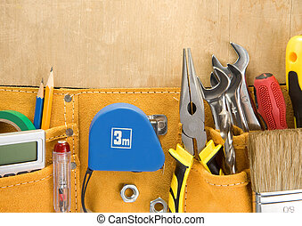 tools in construction belt on wooden background