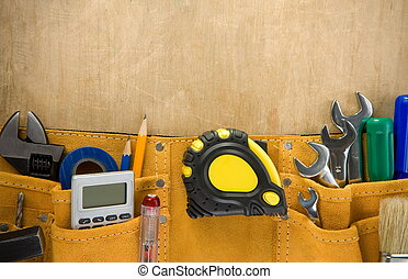 tools in construction belt on wood