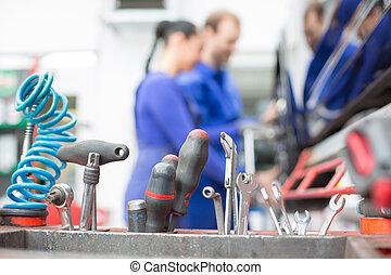 Tools in garage or workshop with mechanics